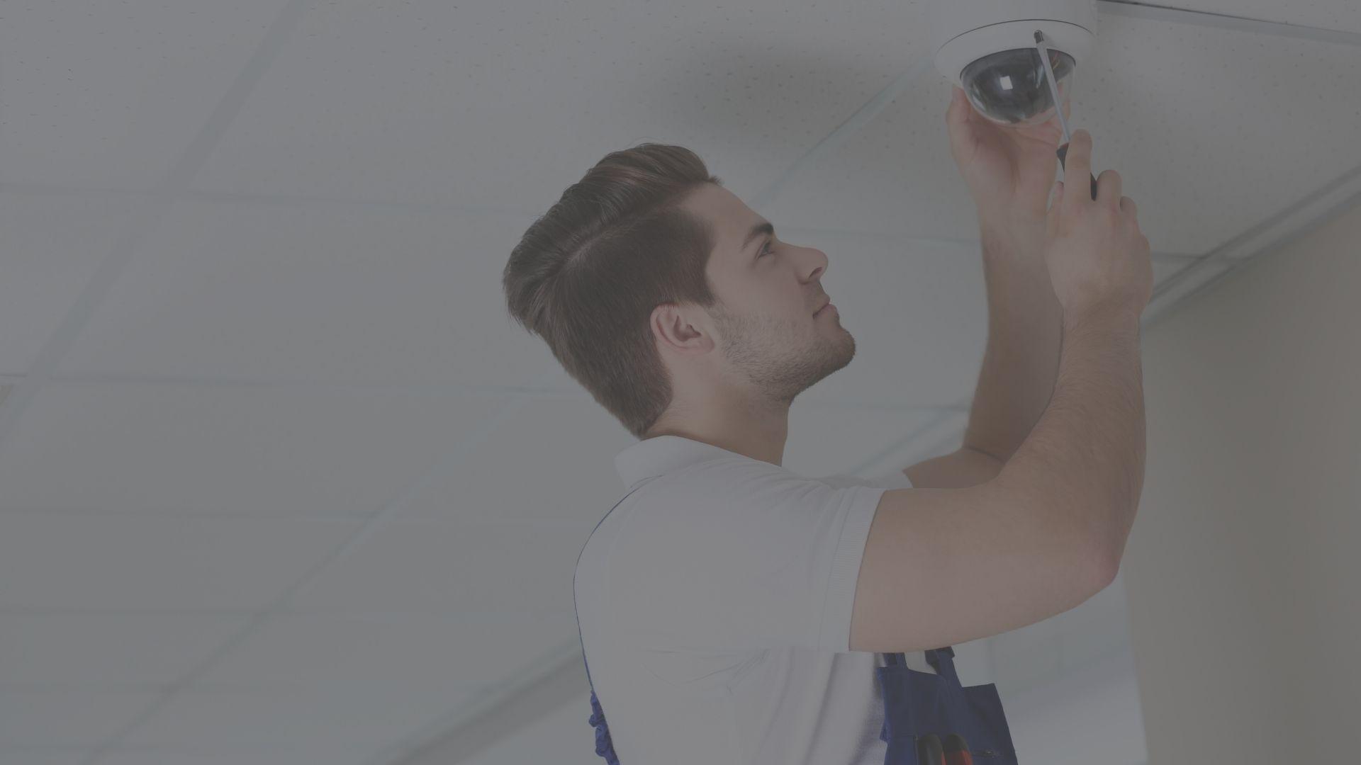 Immagine di un tecnico installatore che sta installando un sistema di sicurezza per abitazioni private o aziende.